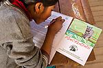 School girl doing quiz on Andean cats during educational outreach program, Ciudad de Piedra, Andes, western Bolivia