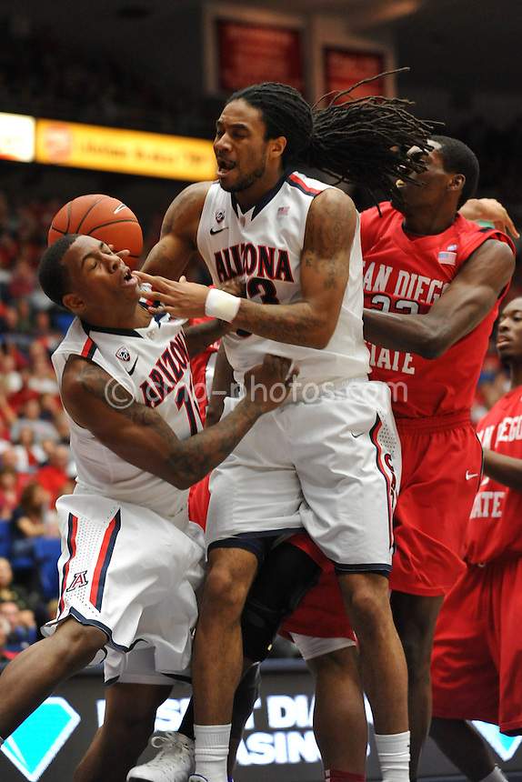 Nov 23, 2011; Tucson, AZ, USA; Arizona Wildcats forward Jesse Perry (middle) and guard Josiah Turner (left) collide going after an offensive rebound in the first half of a game against the San Diego State Aztecs at the McKale Center.  Mandatory Credit: Chris Morrison-US PRESSWIRE