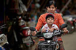 Her child aboard, a woman rides a motorcycle through the Tahan Market in Kalay, a town in Myanmar. This market is located in Tahan, the largely ethnic Chin section of the town. The woman and child are wearing thanaka, a cosmetic paste, on their faces.