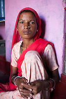 Suki (not her real name), sits for a portrait in her house in Jhaju village, Bikaner, Rajasthan, India on 4th October 2012. Now 20, Suki was married off at age 12, but only went to live with her husband when she was 14. The three sisters, aged 10, 12, and 15 were married off on the same day by their maternal grandfather while their father was hospitalized. Her husband died three years after she moved in, leaving her with a daughter, now 6, and a son, now 4. She has no parents-in-laws and thus returned to her parents house after being widowed because her brother-in-law, who had become the head of the family after his brother's death, had refused to allow Suki to inherit her deceased husband's fair share of agriculture land. Although Suki's father wants her to remarry, she refuses to, hoping instead to be able to support her family through embroidery and tailoring work. The family also makes hand-loom cotton to subsidize their collective household income. Photo by Suzanne Lee for PLAN UK
