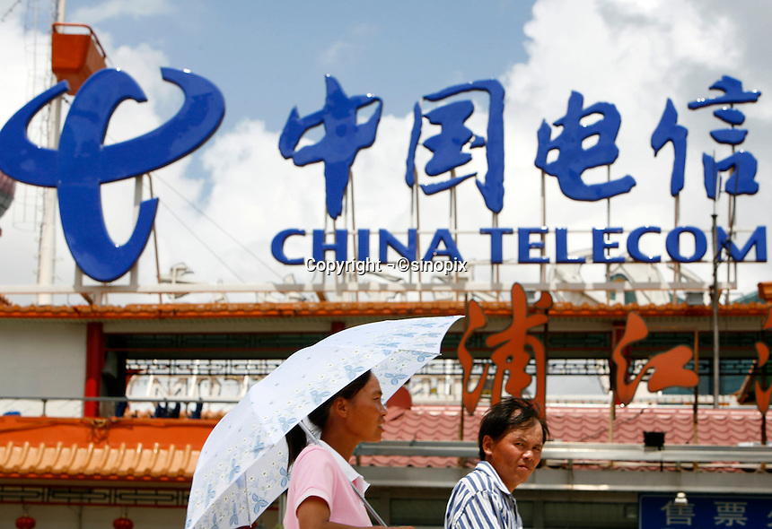 Pedestrians walk past a China Telecom sign in Shanghai, China..