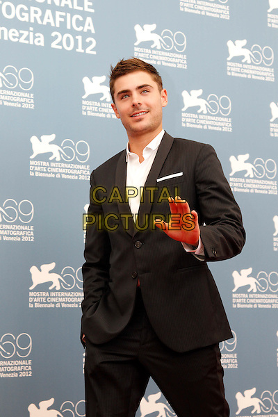 Zac Efron  .'At Any Price' Photocall during The 69th Venice Film Festival at the Palazzo del Casino, Venice, Italy..August 31st, 2012.half length black suit white shirt hands in pockets stubble facial hair palm waving .CAP/IPP/GR.©Gianluca Rona/IPP/Capital Pictures.