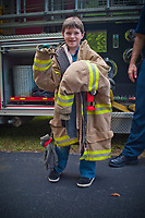 Young boy wears a fire fighter's breakout gear at an emergency services kids expo in Westerville