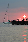 Sailboat Leaving Bayfield Marina with People on Pier Silhouetted against Sun