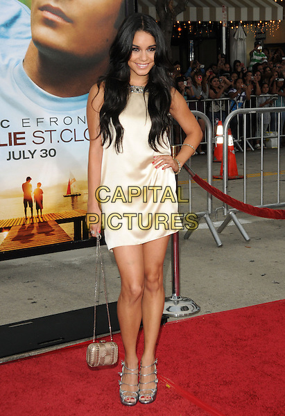 "VANESSA HUDGENS.The World Premiere of ""Charlie St. Cloud"" held at The Regency Village Theater in Westwood, California, USA..July 20th, 2010                                                                                .full length shoes silver triple 3 three straps white cream silk satin dress hand on hip gold bag purse .CAP/RKE/DVS.©DVS/RockinExposures/Capital Pictures."
