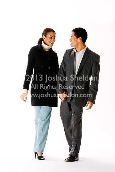 Young couple holding hands and walking on white background