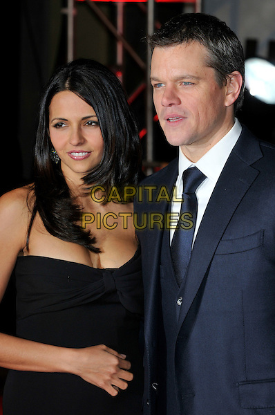 "LUCIANA BARROSO & MATT DAMON.Attending the ""Invictus'"" UK Film Premiere at the Odeon West End cinema, Leicester Square, London, England, January 31st, 2010..arrivals half length married couple husband wife black tie white shirt suit strapless dress hand on tummy stomach navy blue .CAP/PL.©Phil Loftus/Capital Pictures"
