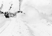 Rotary snowplow clearing snow, possibly at Cumbres.  A passenger train is standing by, waiting for the rotary to clear a path.<br /> D&amp;RG  Cumbres ?, CO