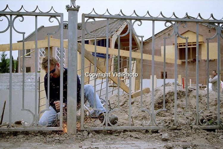 """Foto: VidiPhoto..OPHEUSDEN - Een bouwvakker snijdt met een slijptol de metalen ophanging van het hekwerk kapot. Het hek langs de straat moet tijdelijk verwijderd worden omdat alle ruimte nodig is voor de steigers die straks geplaatst gaan worden. In Opheusden wordt gebouwd aan opmerkelijk grote kerk. Een deel van de oude kerk van de """"Gereformeerde Gemeente in Nederland"""" is gesloopt en wordt nu vervangen door een compleet nieuwe hal. De twee zijbeuken zijn blijven staan. Het uit 1951 daterende gebouw met ongeveer 1700 zitplaatsen, was veel te klein geworden voor de streng orthodoxe kerkelijke gemeente. Het nieuwe gebouw telt straks 2608 zitplaatsen. Met Kerst moet de kerk gereed zijn. De kosten bedragen 5,5 miljoen gulden.."""