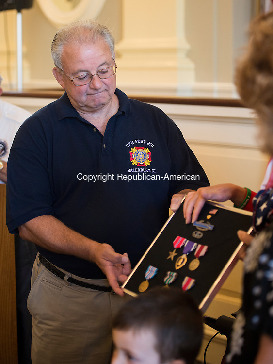 WATERBURY, CT - 26 August 2015-082615EC01-- Vincent DiDominzio, Jr., accepts WWII medals on his deceased father's behalf Wednesday night at Waterbury City Hall. Vincent Didominzio Sr., posthumously received the Bronze Star, the Purple Heart, the Good Conduct Medal and the American Campaign Medal. The new medals were secured by Congresswoman Elizabeth Esty after the family reached out to the local V.F.W. post to help replace the missing ones. Erin Covey Republican-American.