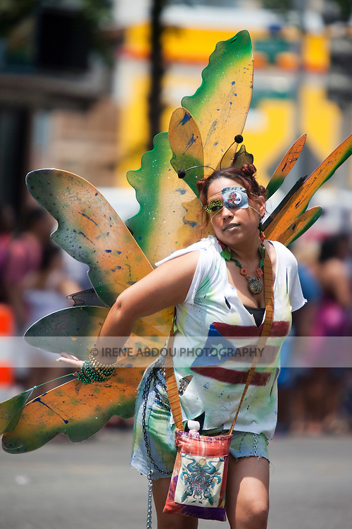 The DC Caribbean Carnival is held annually in Washington, DC.  Launched by a large Caribbean-style parade with dancers in traditional Caribbean carnival costumes, the festival promotes and educates the community about Caribbean arts, crafts, and culture.  Here, a woman in a butterfly costume crashes the parade!
