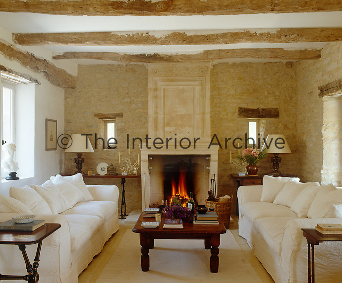 In this living room the rustic beams and mellow stone walls have been sympathetically restored with a carved stone fireplace as an arresting focal point in an otherwise simple and elegant arrangement