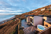 BNPS.co.uk (01202 558833)<br /> Pic: UniqueHomestays/BNPS<br /> <br /> Pictured: There is a patio, a hot-tub and shower.<br /> <br /> A couple who spent £450,000 on turning a 'rotting shed' into an exclusive seaside bolthole hope to recoup their money - by renting it out for £3,150 a week. <br /> <br /> Tracey Gilpin and Peter Burridge went out on a limb when they bought the 60-year-old wooden shack for a whopping £220,000.<br /> <br /> Despite its ramshackle condition, the cabin could command such a hefty asking price as it is located halfway up a cliff with stunning views of Whitsand Bay in Cornwall.<br /> <br /> But in order to make the coastal chalet a viable holiday let the couple had to demolish it and build a new one from scratch.