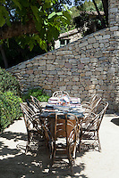 An outdoor dining area benefits from the shade of a fig tree on the terrace