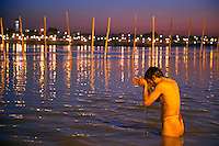 India. Uttar Pradesh state. Allahabad. Maha Kumbh Mela. An Indian Hindu devotee takes a holy dip and prays in Sangam at night. The man wears a Janeu which is a consecrated thread worn by each and every Hindu Brahmin of India. The Kumbh Mela, believed to be the largest religious gathering is held every 12 years on the banks of the 'Sangam'- the confluence of the holy rivers Ganga, Yamuna and the mythical Saraswati. In 2013, it is estimated that nearly 80 million devotees took a bath in the water of the holy river Ganges. The belief is that bathing and taking a holy dip will wash and free one from all the past sins, get salvation and paves the way for Moksha (meaning liberation from the cycle of Life, Death and Rebirth). Bathing in the holy waters of Ganga is believed to be most auspicious at the time of Kumbh Mela, because the water is charged with positive healing effects and enhanced with electromagnetic radiations of the Sun, Moon and Jupiter. The Maha (great) Kumbh Mela, which comes after 12 Purna Kumbh Mela, or 144 years, is always held at Allahabad. Uttar Pradesh (abbreviated U.P.) is a state located in northern India. 7.02.13 © 2013 Didier Ruef