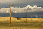 Clouds, power lines, snow drift fence across the eastern Wyoming plains