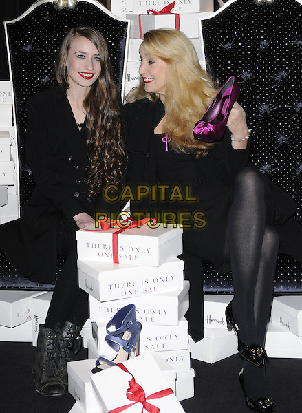 ELIZABETH JAGGER, JERRY HALL.open Harrods Winter Sale, knightsbridge, london, England 27th December 2010.lizzie lizzy full length mother mom mum daughter family black dress coat jacket  sitting boxes tights gifts presents smiling holding purple shoe profile .CAP/CAN.©Can Nguyen/Capital Pictures.