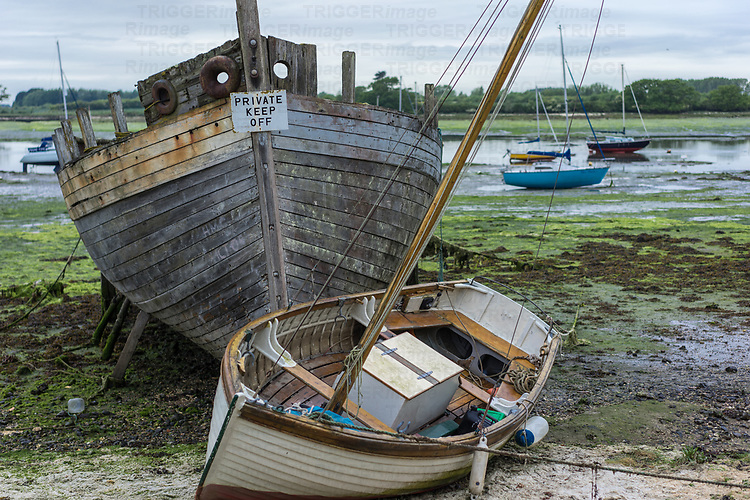 A small sailing dinghy beside a large rotting hulk of a boat