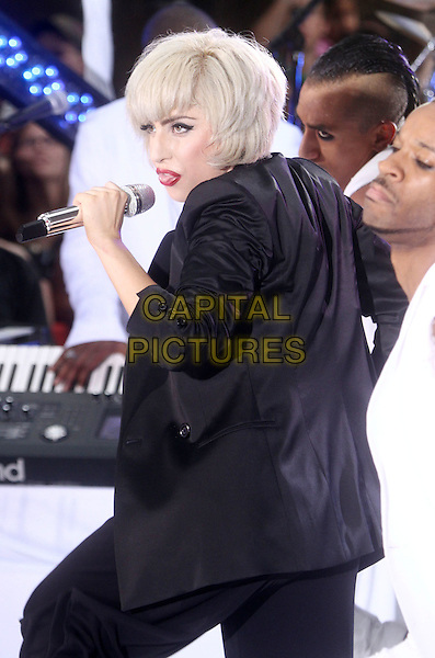 "LADY GAGA (Stefani Joanne Angelina Germanotta) .performs live on NBC's ""TODAY"" Show at Rockefeller Center, New York, NY, USA, 9th July 2010..on stage music concert gig half length black jacket blazer microphone singing suit back rear behind profile side .CAP/ADM/AC.©Alex Cole/AdMedia/Capital Pictures."