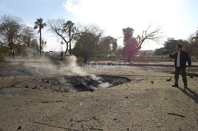 BAGHDAD, IRAQ:  A man films a crater left from an explosion outside the Sheraton Hotel, January 25, 2010...At least 36 people have died in three large explosions apparently targeting hotels in the heart of Iraq's capital..More than 70 people were injured in the Baghdad blasts, which officials said were caused by suicide car bombers.  They struck near the Sheraton, Babylon and Hamra hotels, which are popular with Western businessmen and media....Photo by Qeas Kazm/Metrography