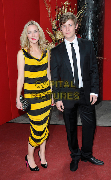 ALICE COULTHARD & GUEST.Arrivals - the British Soap Awards 2009, BBC Television Centre, Wood Lane, London, England..May 9th 2009.soaps tv full length black yellow bee wasp striped stripes sleeveless suit dress clutch bag shoes .CAP/FIN.©Steve Finn/Capital Pictures.