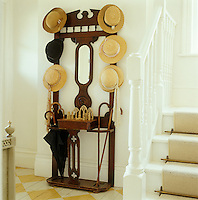 An antique hat stand in the hall sports a selection of straw hats, umbrellas and walking sticks