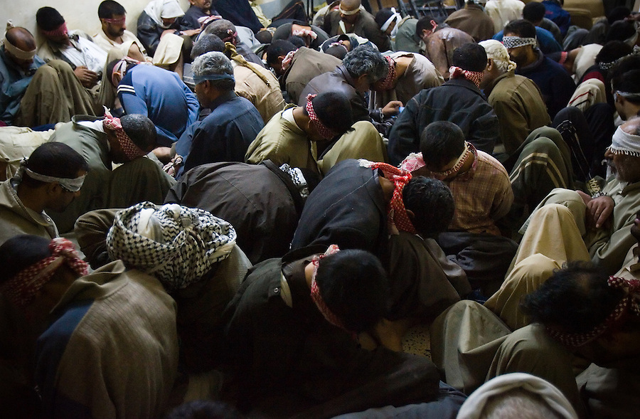 Scores of detainees - nearly 200 in all swept up in an Iraqi Army security sweep - wait, seated and blindfolded in the rooms and hallways of the Diyala provincial court in Baqubah on Mon. Dec. 4, 2006. American advisors and Iraqi judicial officials have repeatedly urged Iraqi security forces to carry out targeted raids rather than detaining large portions of households and villages in an effort to capture suspected insurgents.<br />