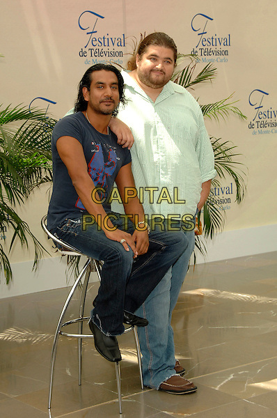 """NAVEEN ANDREWS & JORGE GARCIA.Photocall promoting the television series """"Lost"""" on the fourth day of the 2008 Monte Carlo Television Festival held at Grimaldi Forum, Monaco, Principality of Monaco..June 11th, 2008.full length blue t-shirt green striped stripes t-shirt stool arm on shoulder stubble facial hair sitting jeans denim.CAP/TTL .© TTL/Capital Pictures"""
