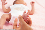 Newborn baby girl 12 days old closeup of feet reflex Babinski mother strokes side of foot and toes fan out