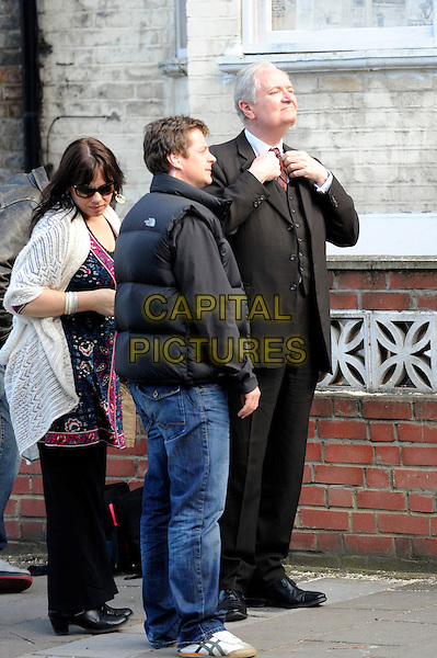 """JIM BROADBENT.Filming on the set of """"Any Human Heart"""", Dalston, East London, England..*EXCLUSIVE ALL ROUNDER*.April 8th, 2010.film movie acting full length brown suit black tie adjusting  .CAP/IA.©Ian Allis/Capital Pictures."""