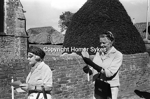 Sandwich Kent England 1975. August 24th St Batholomew's Day Bun Race. The Bartlemas Bun Race. Lady Mayoress hands out buns at end of race. These two ladies about to attend the church service carrying candles.