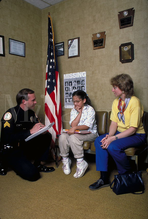 Policeman talks to child as mother watches.