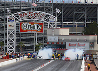 Apr 10, 2015; Las Vegas, NV, USA; NHRA pro stock driver Erica Enders-Stevens (right) does a burnout alongside  Chris McGaha during qualifying for the Summitracing.com Nationals at The Strip at Las Vegas Motor Speedway. Mandatory Credit: Mark J. Rebilas-