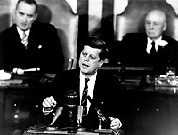 """Washington (DC) USA - May 25, 1961 File Photo - President John F. Kennedy in his historic message to a joint session of the Congress, on May 25, 1961 declared, """"...I believe this nation should commit itself to achieving the goal, before this decade is out, of landing a man on the Moon and returning him safely to the Earth."""" This goal was achieved when astronaut Neil A. Armstrong became the first human to set foot upon the Moon at 10:56 p.m. EDT, July 20, 1969. Shown in the background are, (left) Vice President Lyndon Johnson, and (right) Speaker of the House Sam T. Rayburn."""