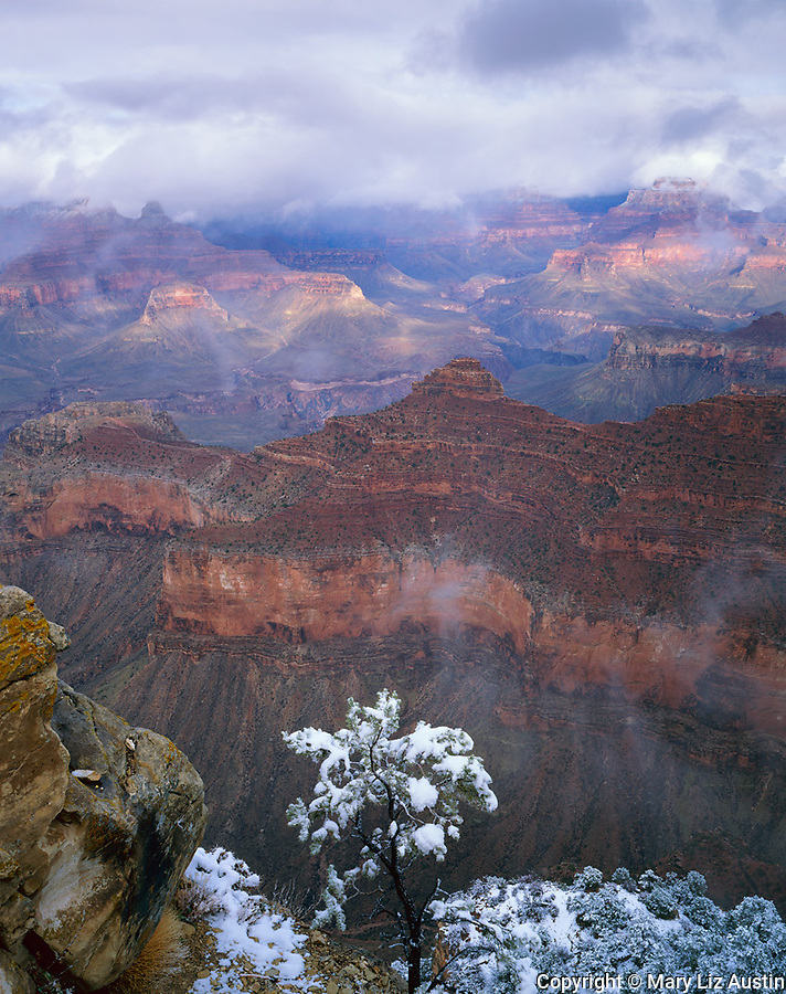 Grand Canyon National Park, AZ   <br /> Sunset light breaks through clearing winter storm clouds with Cedar Ridge and O'Neill Butte in the foreground from Mather Point at the South Rim