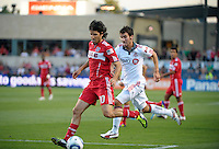 Chicago midfielder Sebastian Grazzini (10) takes a shot with Toronto midfielder Nathan Sturgis (11) in pursuit.  The Chicago Fire defeated Toronto FC 2-0 at Toyota Park in Bridgeview, IL on August 21, 2011.