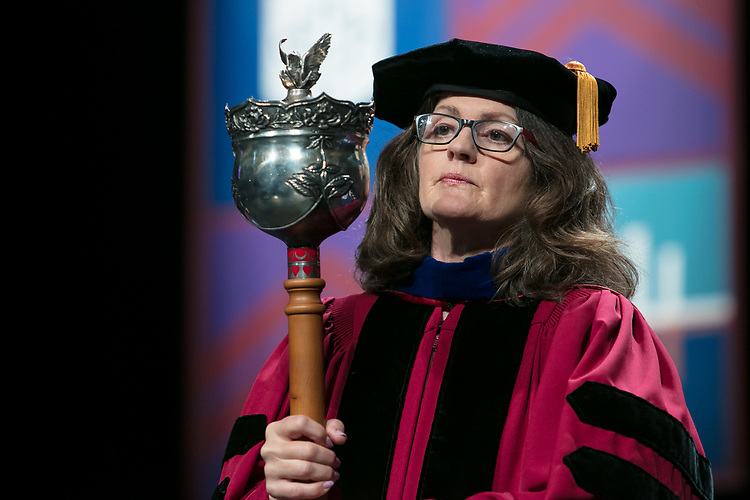 Corinne L. Benedetto, associate professor and associate dean, carries the university mace during the procession Saturday, June 10, 2017, during the DePaul University School for New Learning commencement ceremony at the Rosemont Theatre in Rosemont, IL. (DePaul University/Jeff Carrion)