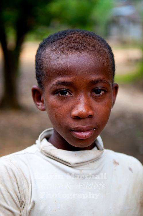 Young Malagasy boy poses for the camera whilst selling goods at the market. Diego Suarez - Northern Madagascar.
