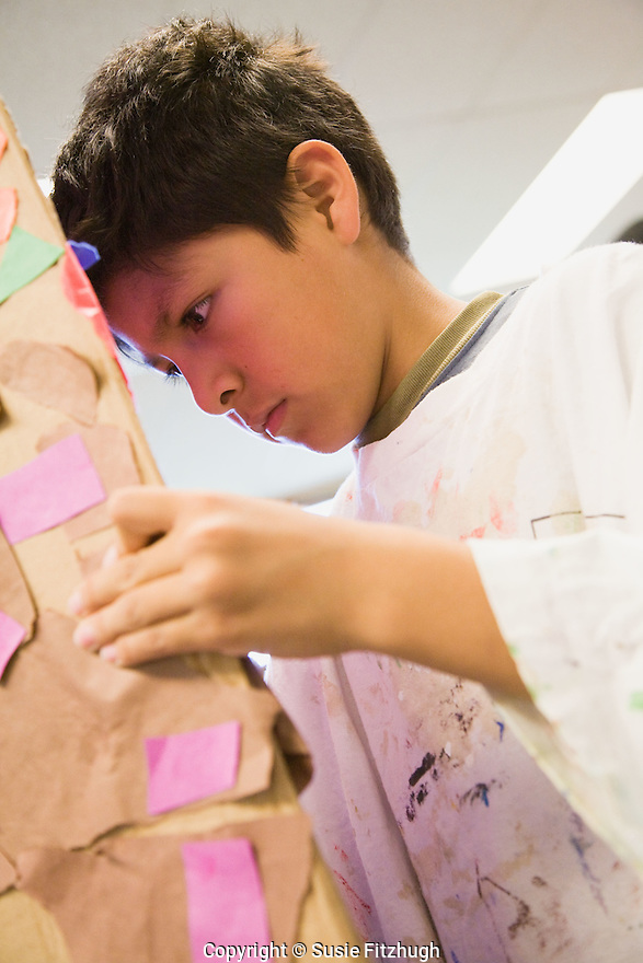 At the YMCA CLC at Bailey Gatzert Elementary School:  Tomas Oliva's Visual Arts students work with him to make a mural; a paper collage showing the day on one side and the night on the other.