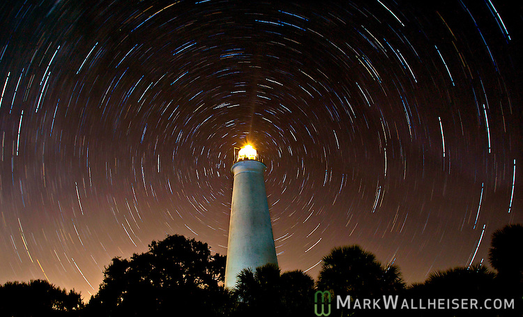 A photograph of the stars in the winter sky as they swirl around the north star over the St Marks lighthouse in this time exposure at the Saint Marks National Wildlife Refuge in Wakulla County Florida near Tallahassee.