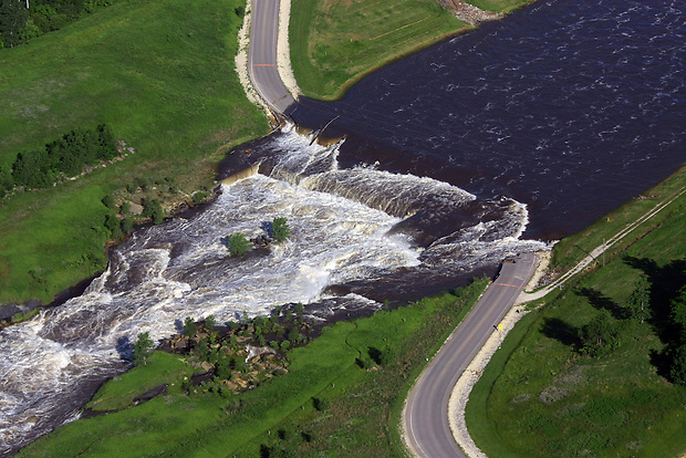 A road is washed as a gorge is carved by flow from the Saylorvile Lake emergency spillway during flooding Saturday, June 14, 2008.