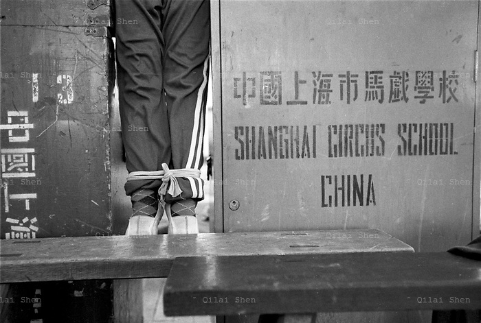QSFeature01Acrobats003 20010414 SHANGHAI, CHINA: A stdent with legs tied together practices hand-stands between two stage prop trunks at the Shanghai Circus School in Shanghai, China 14 April 2001. Traditional entertaiment such as acrobatic shows are loosing audiences and popularity in China, and the students will likely face a tough time  when they finally finish six years of grueling training..Photo by: Qilai Shen