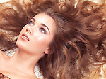 Beauty portrait of a young woman with soft natural look lying down with her long hair spread around her