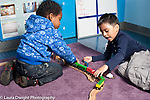 Education Preschool Headstart 3 year olds two boys playing together with train set