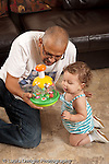 13 month old baby girl at home with father who is her primary caregiver interested as he talks to her and shows her how new toy works vertical