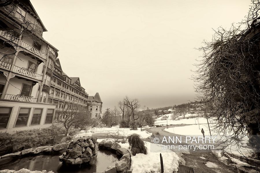 NEW PALTZ - MARCH 14: Mohonk Mountain House wide angle winter view with the historic resort inn at one side, and path with snow on ground, and boulder wall with dead vines on other side, on overcast morning of March 14, 2010 at New Paltz, New York, USA. Monochrome with sepia tone. For Editorial Use Only.