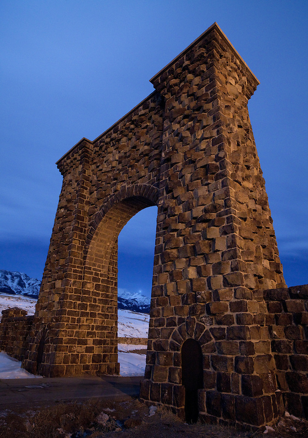 Clouds and the distant landscape of Yellowstone are seen during the night through the arched park gate in winter.
