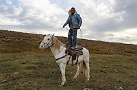 Edgar Oscanoa demonstrates Dot's calm nature by standing on his back.  The former mustang was trained at a correctional facility and works on a sheep ranch in Wyoming.