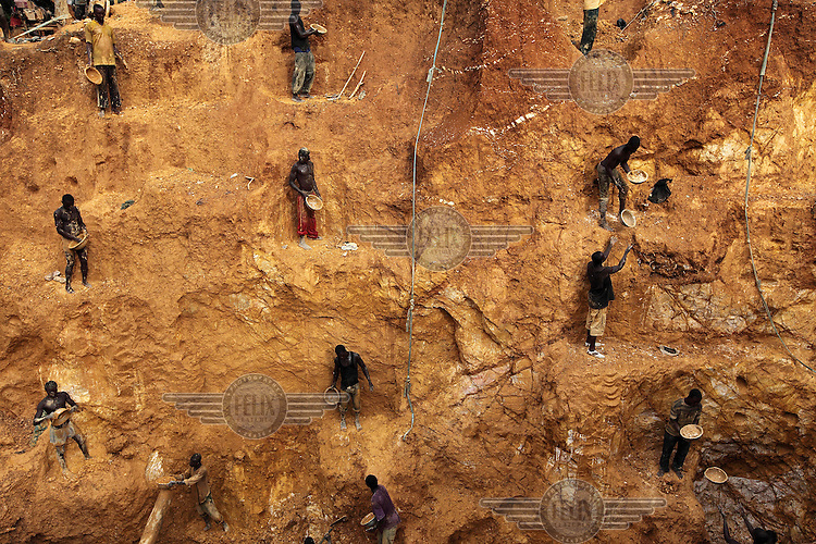 Young men work at various levels of a wall on a gold mining site in Obuasi. Many unemployed young people have taken to working as illegal artisanal gold miners known as galamseys in Ghana.