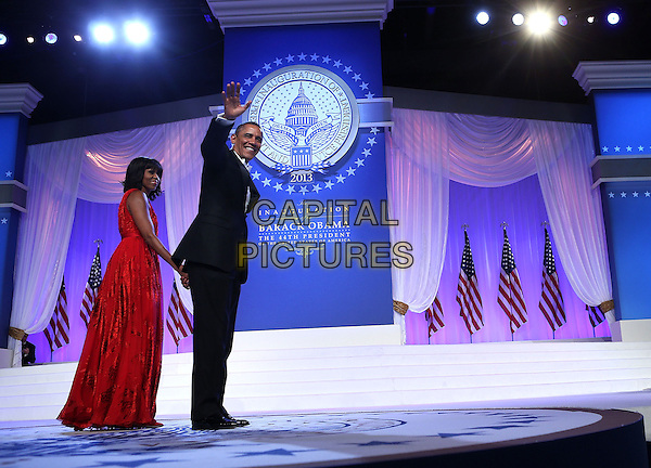 Michelle Obama & Barack Obama.2013 Inauguration Ball, Washinton D.C., USA..January 21st, 2013.full length black suit tuxedo red dress profile holding hands married husband wife arm waving   .CAP/ADM/CNP/AW.©Alex Wong/CNP/AdMedia/Capital Pictures.